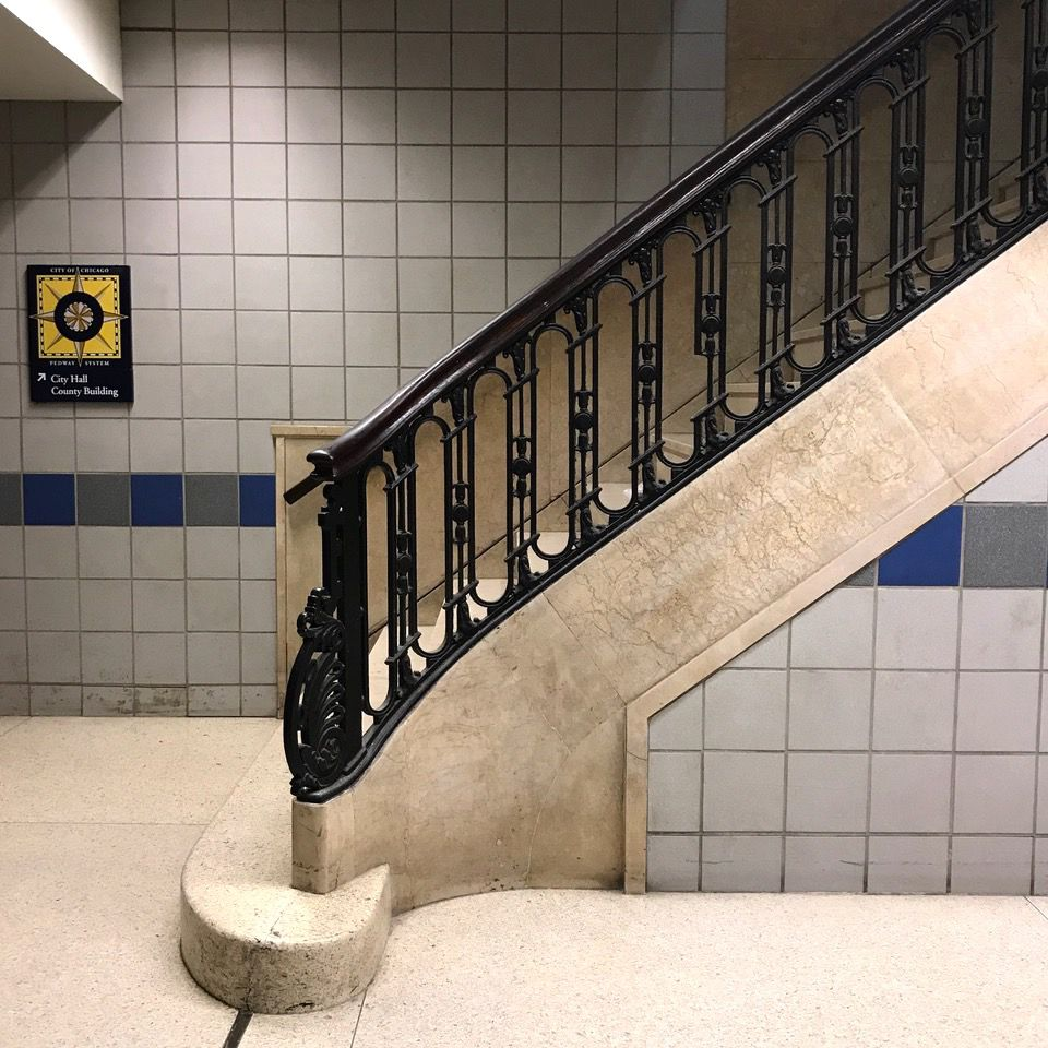 A staircase with marble and tiles. A black railing.