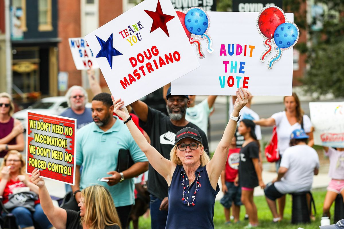 """A woman amid a crowd of protesters holds up two colorful signs, one reading """"Audit the vote"""" and another reading """"Thank you Doug Mastriano."""""""