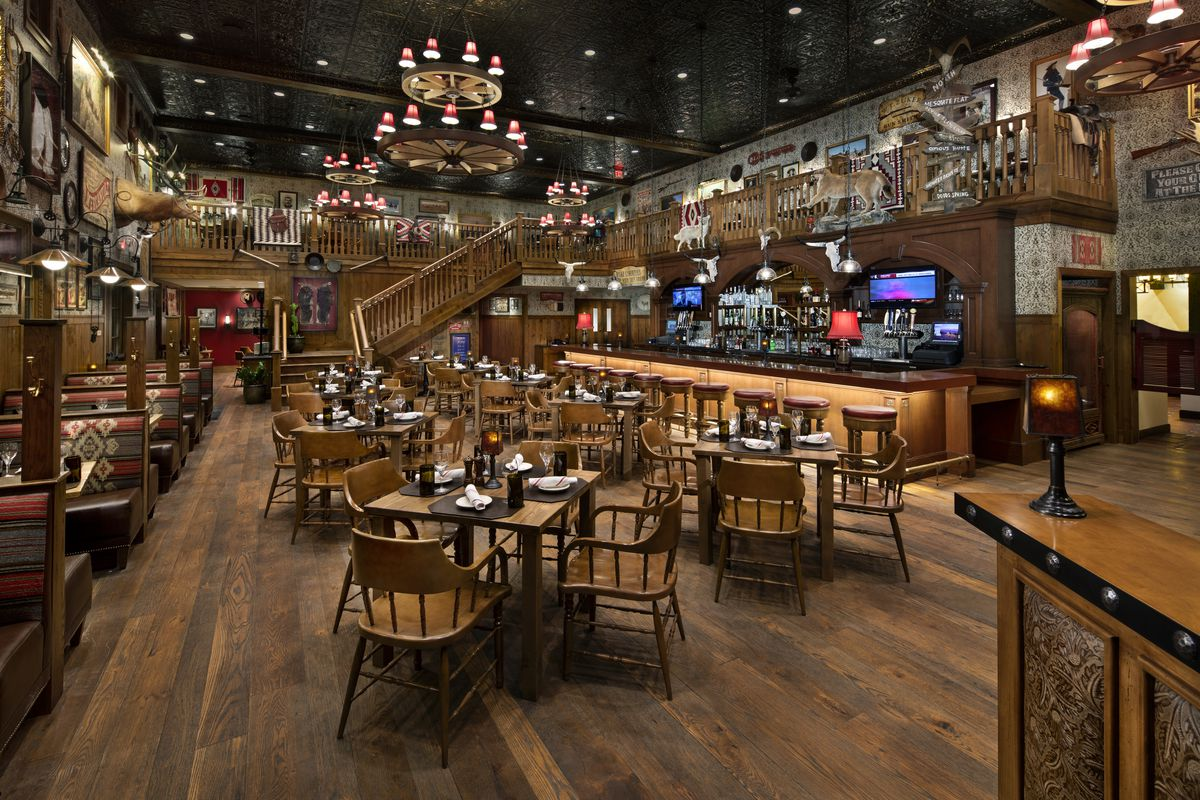 A two story cowboy bar with rustic touches and animal pelts.