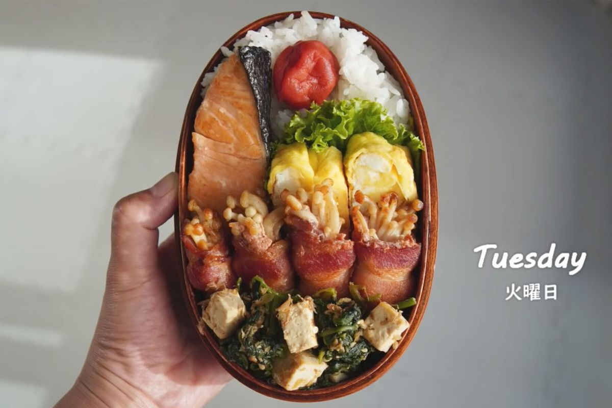 Hand holding up a full bento box with rice, egg, shrimp, and tofu dishes.