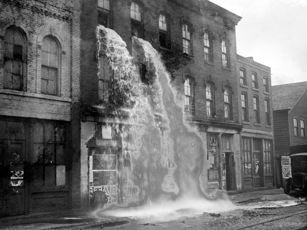 Streams of confiscated liquor pour out of upper windows of three-story storefront in Detroit during Prohibition.