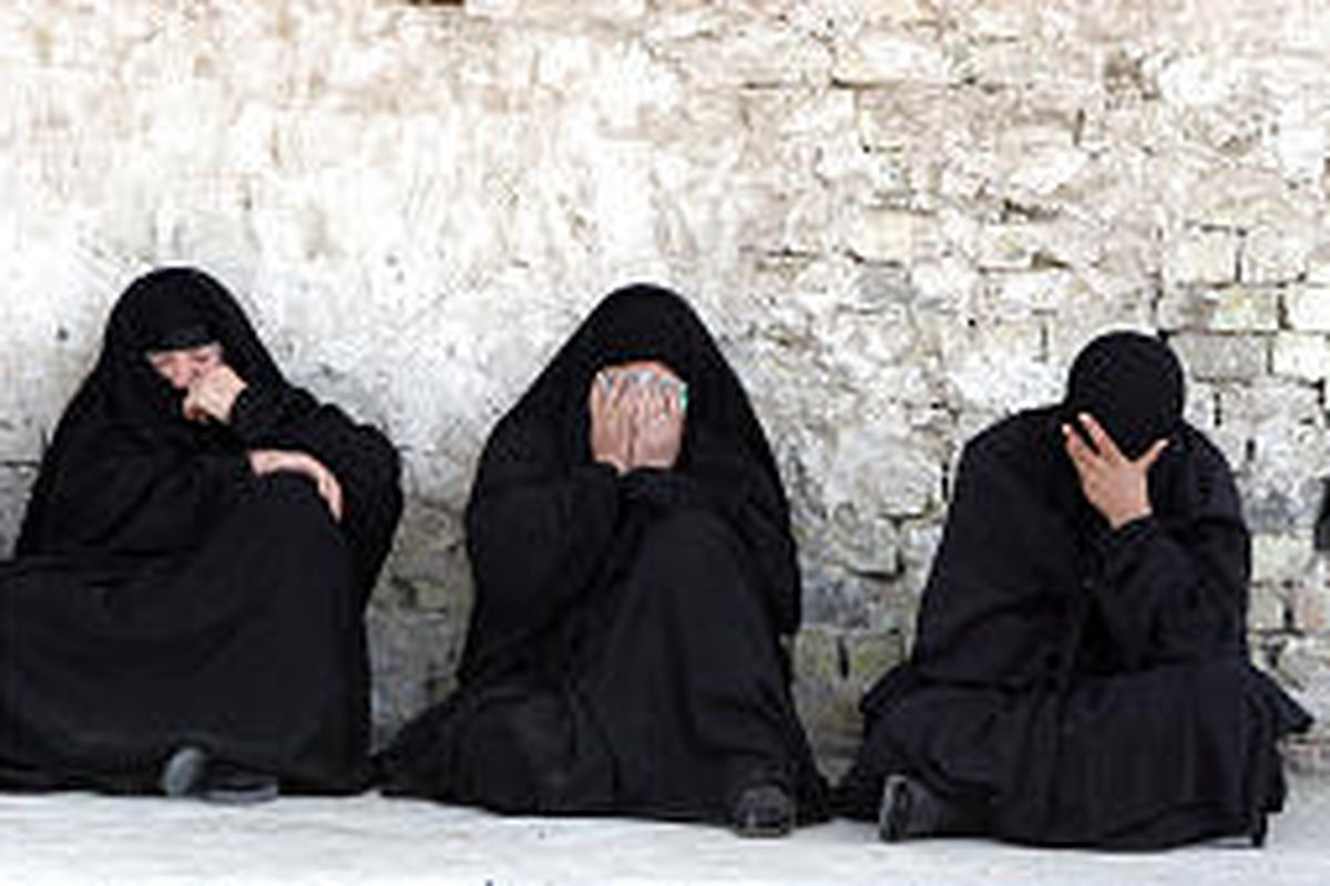 Iraqi women mourn outside a Baghdad hospital after a suicide bomber detonated himself near a restaurant frequented by police officers, killing 35 and wounding 25.