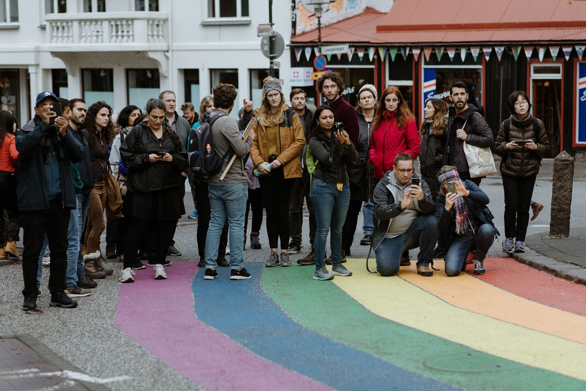Tourists on a street painted with rainbow stripes take pictures with their cellphones.