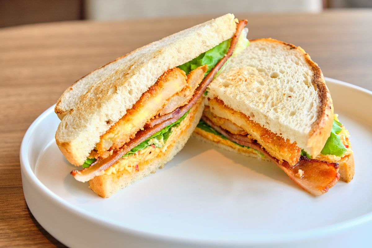 A fried green tomato sandwich on toasted white bread with bacon, lettuce, and fried egg cut in half on a white plate