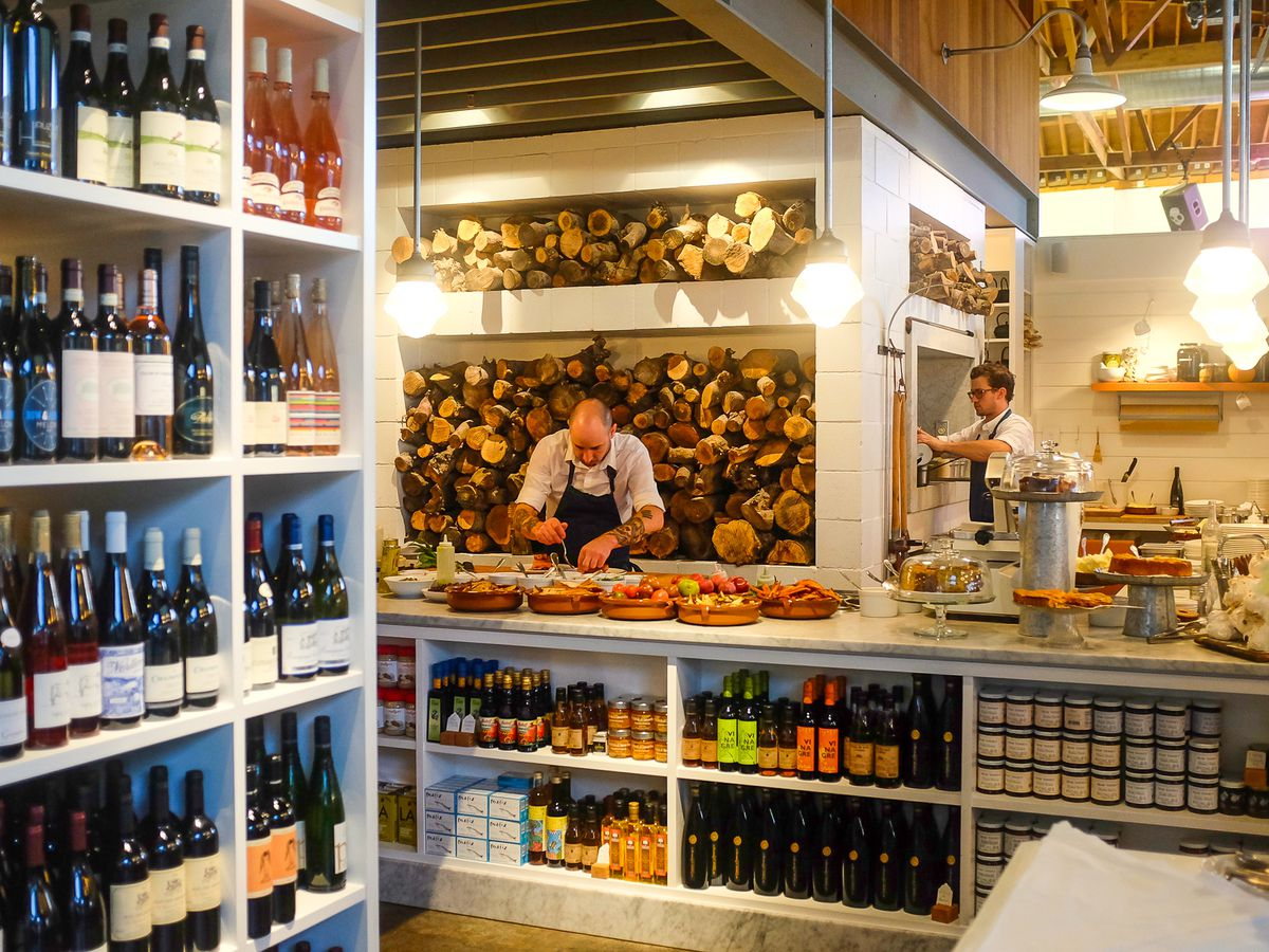 The interior of The Whale Wins, with a chef preparing a dish on a counter.
