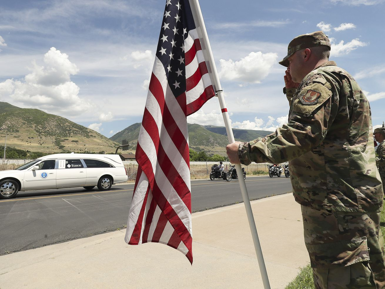 "Tech Sgt. Joseph Easley salutes as a hearse carrying the body of U.S. Air Force 1st Lt. Kenneth ""Kage"" Allen drives by Heritage Park in Farmington on Friday, June 26, 2020. Allen, a fighter pilot, died after crashing off the coast of northern England during a training exercise on Monday, June 15."