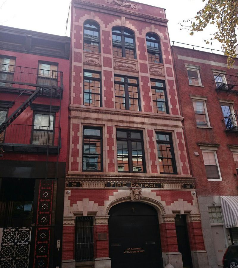 The exterior of 84 West 3rd Street in New York City. The facade is red brick and there are multiple windows. There is a sign above the arched entrance that reads: Fire Patrol.