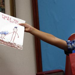 Kamden Gill, 5, holds a drawing and a present for Dr. Steven Mobley at the Surgical Specialty Center in Salt Lake City on Friday, Sept. 23, 2011. Dr. Mobley performed an otoplasty to fix Kamden's protruding ears.