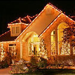 A home in Draper glows after Vance Brand installed lights Nov. 8. Some homes are so tall that lifts are used, rather than ladders, to string lights. The operation is labor-intensive, hazardous.