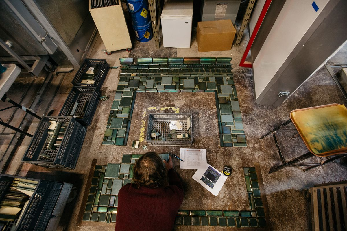 A worker hovers over a tile pattern for a fireplace.