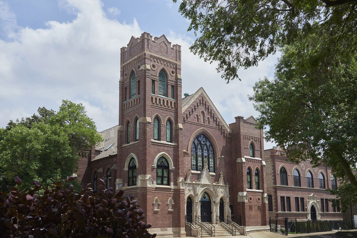 An exterior view of a brick and limestone church with neo gothic architecture including arched windows and a corner belltower.