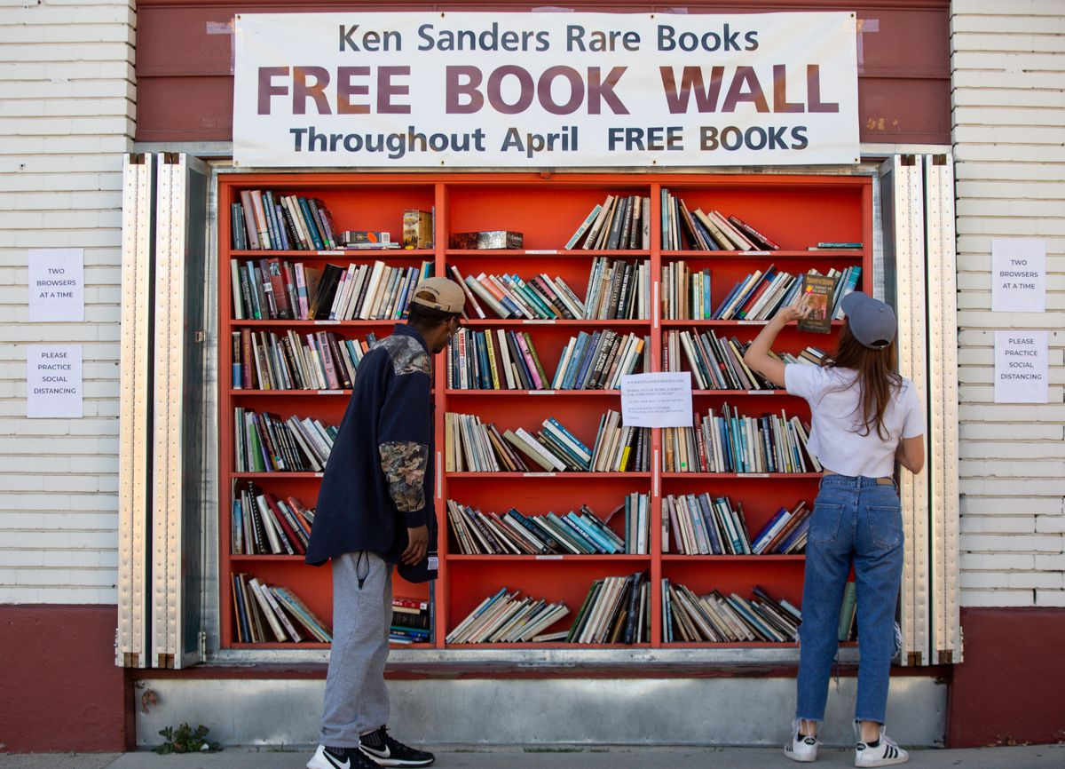 """People practice social distancing while picking up books at Ken Sanders Rare Books in Salt Lake City on Saturday, April 18, 2020. The book wall's normally dollar books are being given away amid the COVID-19 pandemic. The sign in the center asks, """"Bored, out of work, looking for something to read?"""""""