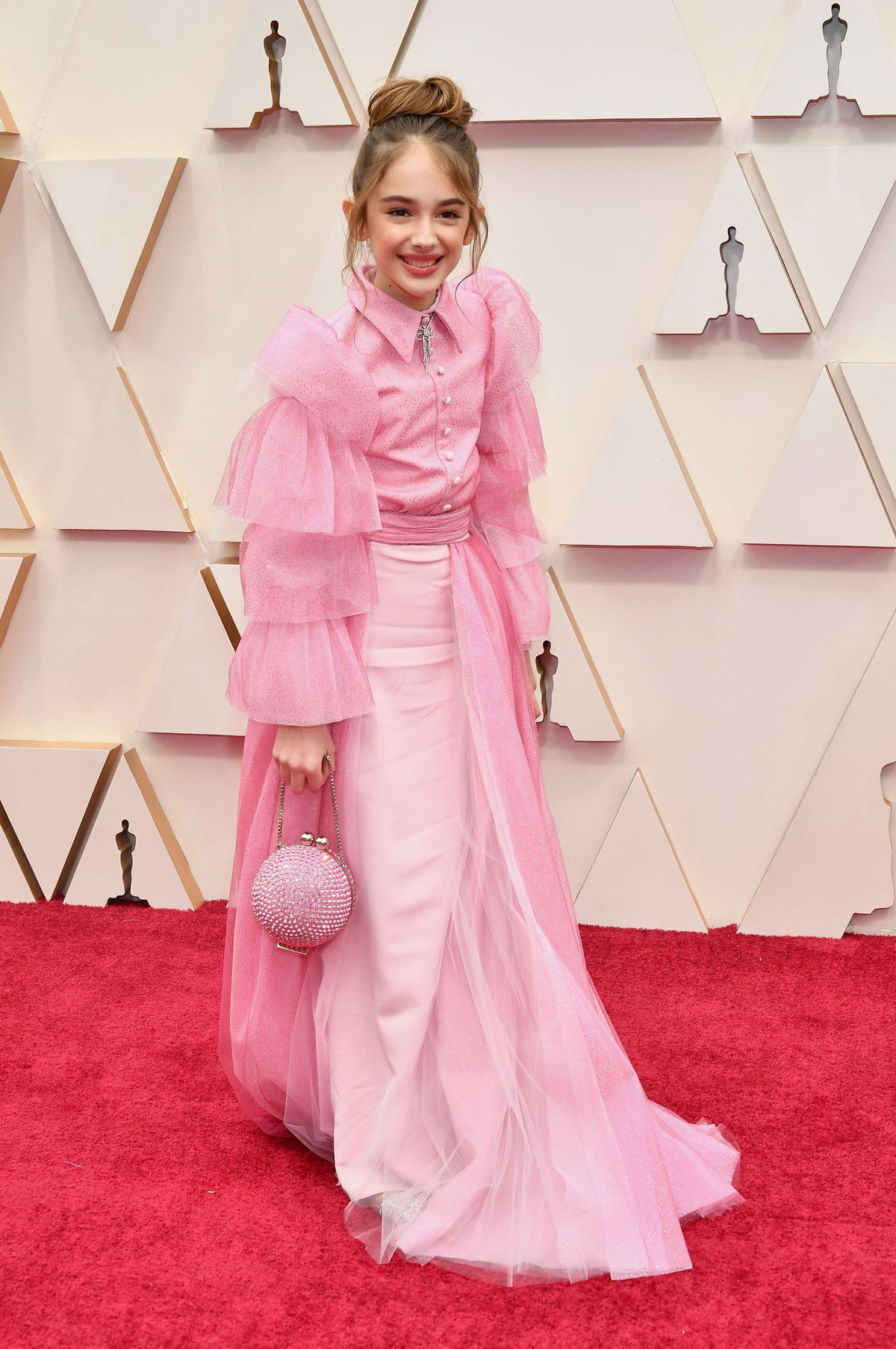 Julia Butters wears a pink dress by Christian Siriano on the red carpet.