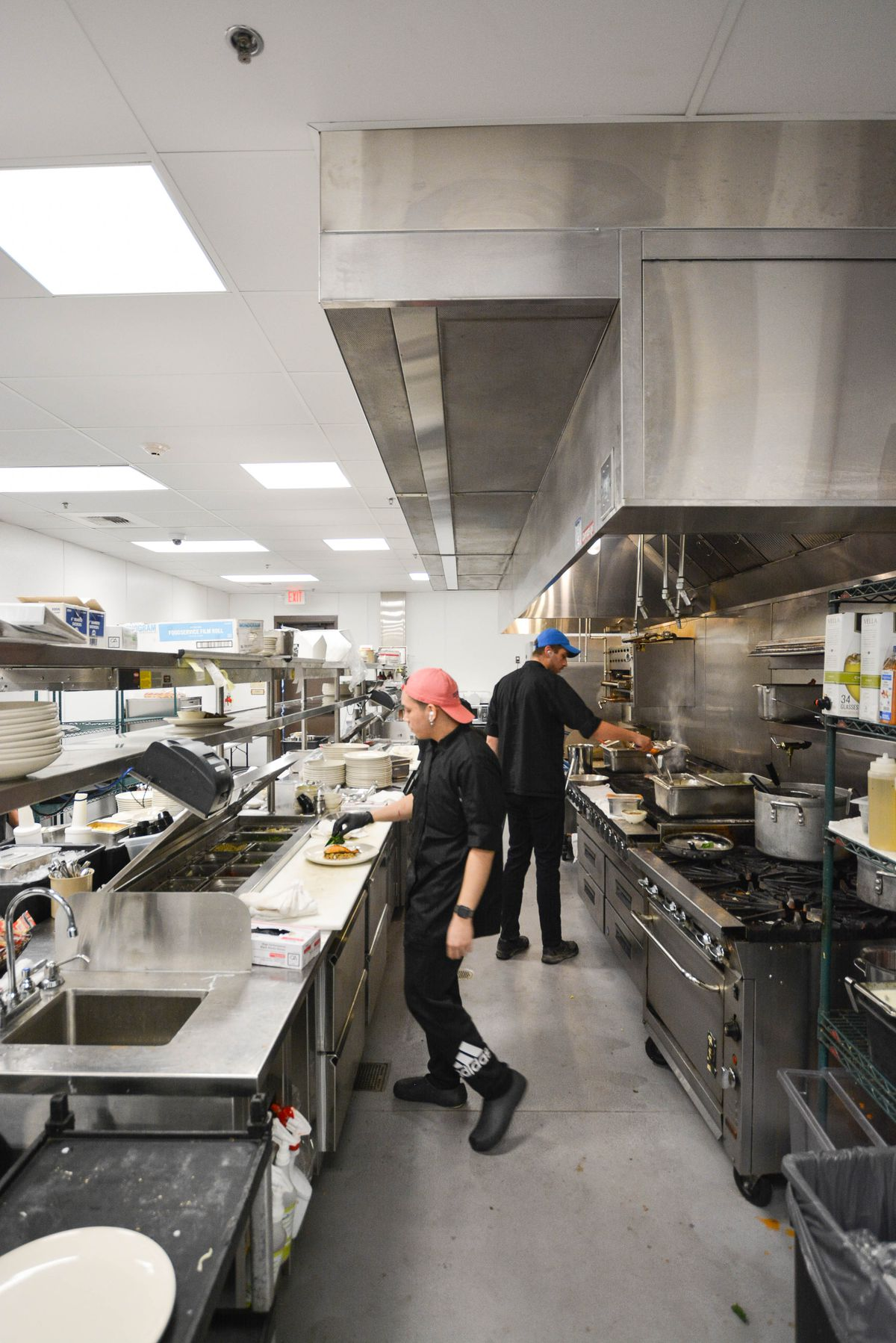 A worker with headphones prepares food inside of a bright kitchen.