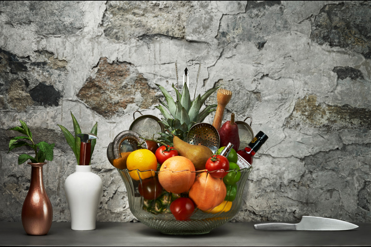 A glass bowl of fruit in front of a concrete wall.