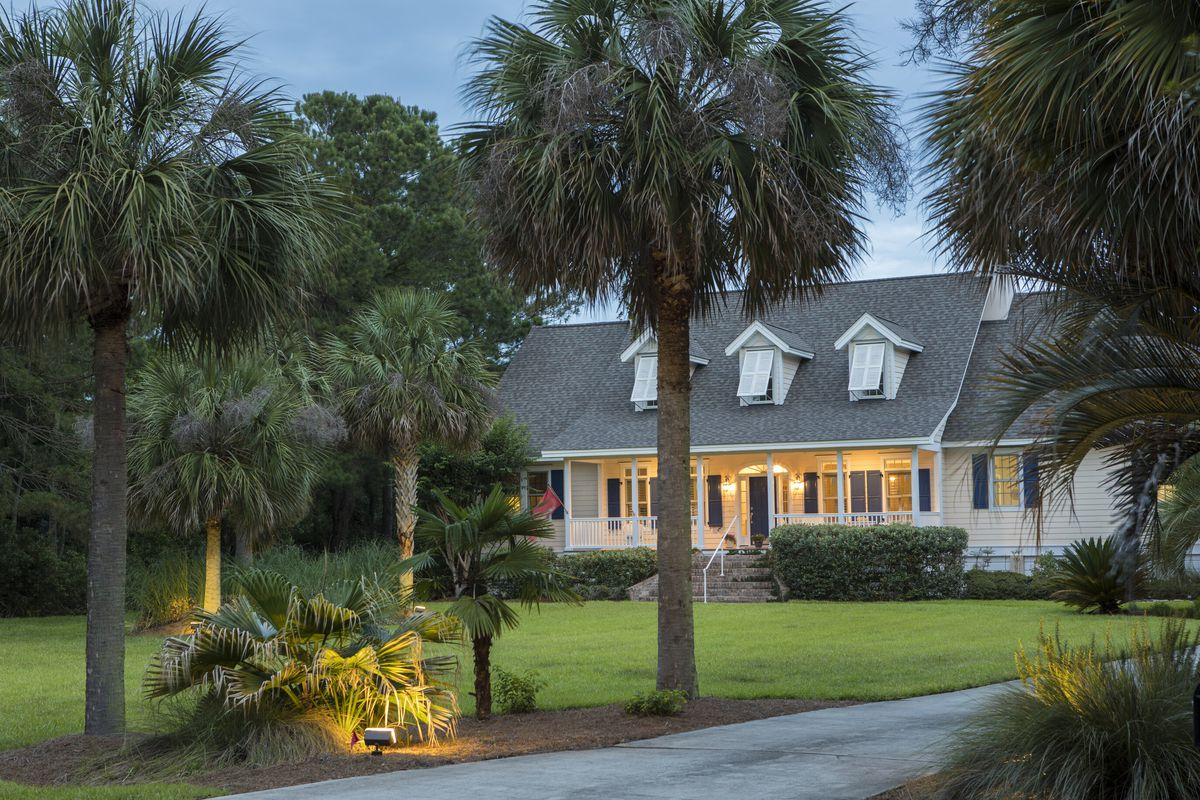 A white home with large palm trees lit up at twilight.