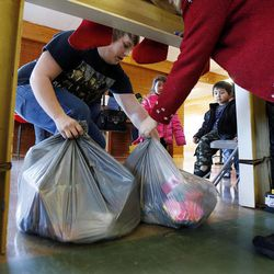 Austin Hawks pulls bags of gifts for Jeanette, Meilissa (CQ) and Angel Ramirez during 2014 Operation Chimney Drop at Head Start in Salt Lake City, Monday, Dec. 15, 2014.
