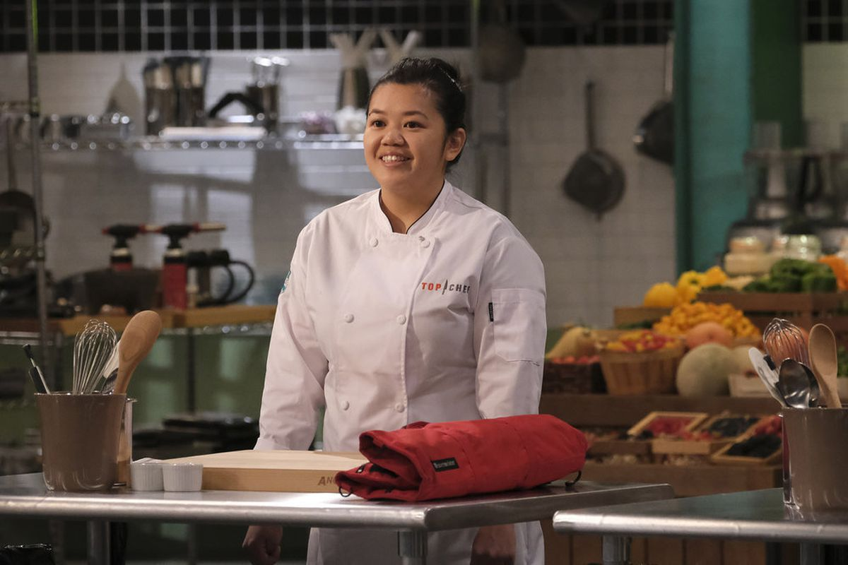 A woman in a white chef's coat stands in a kitchen