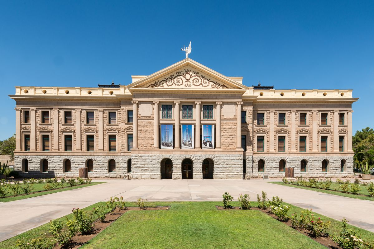 The exterior of the Arizona State Capitol. The facade is tan. There are many windows. In the foreground is a courtyard with garden areas.