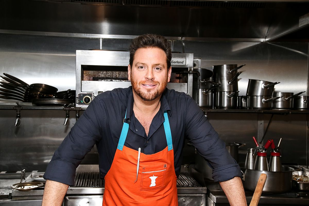 Chef Scott Conant smiling while wearing an orange apron and black shirt.