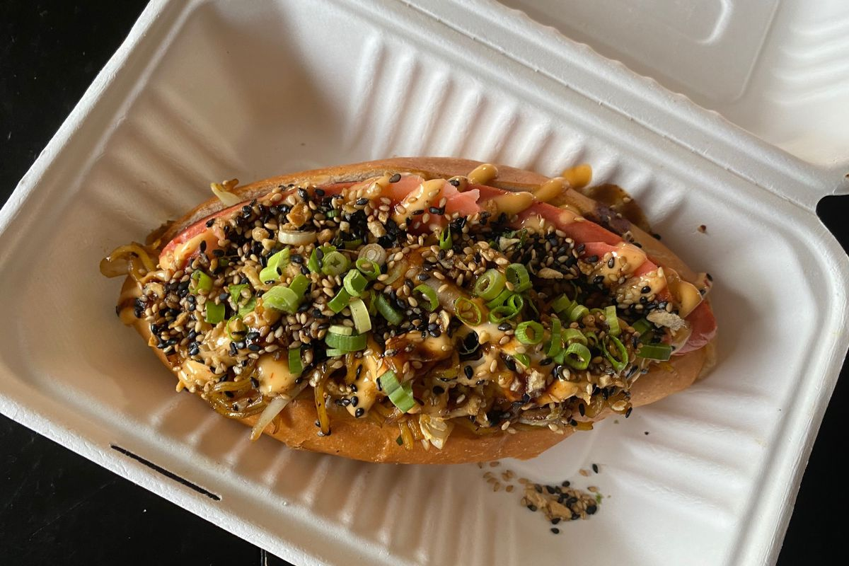A yakisoba pan in a takeout box: a fat torpedo roll overstuffed with stir-fried noodles and garnished with scallions and sesame seeds