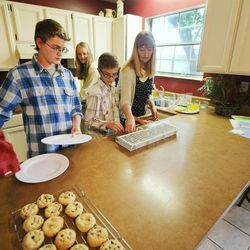 The Evans children put the dishes away after dinner Monday, May 11, 2015, as they spend time together at home in Murray.