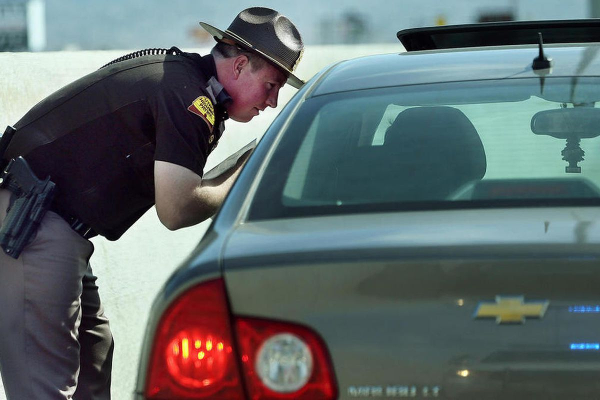 FILE - Trooper Nick Swallow talks with a driver after pulling them over for speeding.