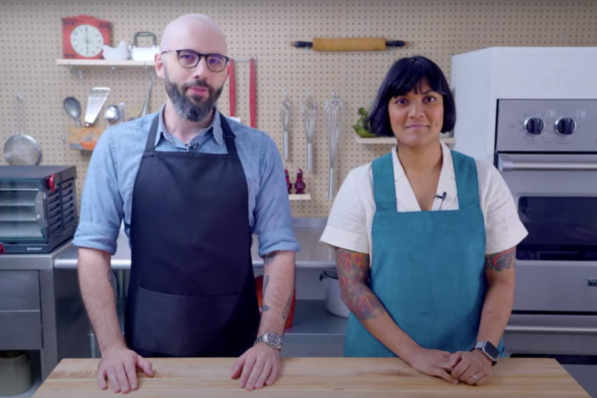 A white man in a blue apron and a brown woman in a teal apron standing side by side in a kitchen