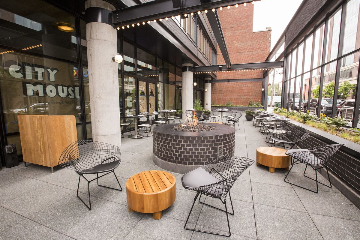 A patio area with a deck, patio chairs, wooden, round tables.