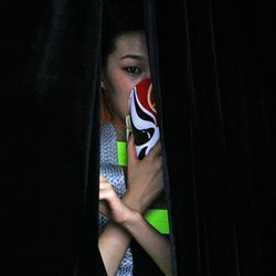 A Chinese model peeks out from behind curtains before a fashion show promoting the relationship between Beijing and the Italian Lazio region in Beijing, China, Wednesday.