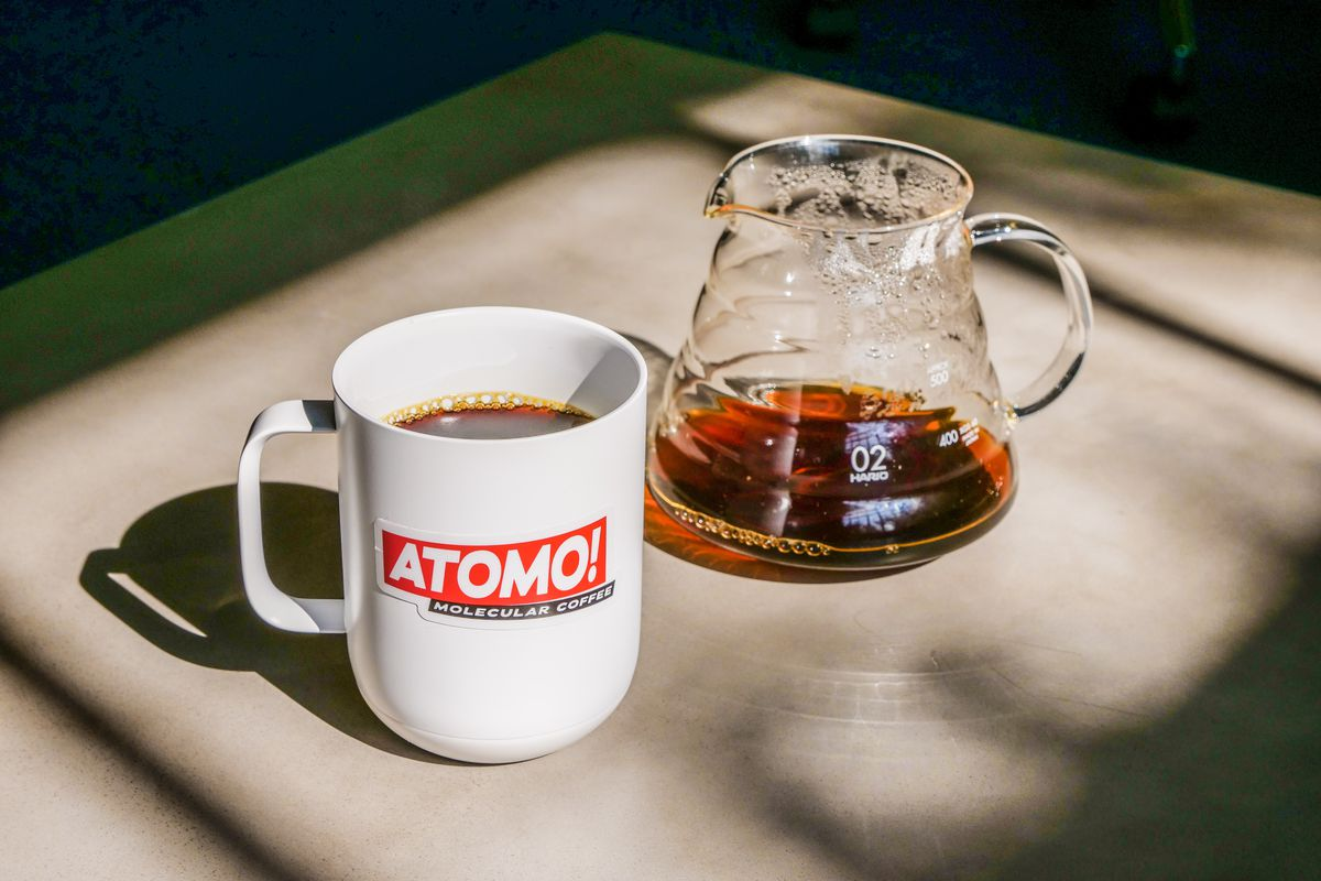 A white mug with the Atomo logo in red next to a glass beaker filled partly with coffee.