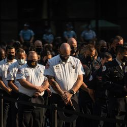 Members of the Chicago Fire Department bow their heads in prayer during the commemoration of the 20th anniversary of 9/11 at the Richard J. Daley Plaza in the Loop, Saturday morning, Sept. 11, 2021.