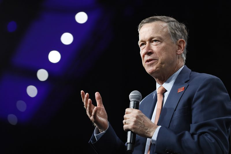 John Hickenlooper onstage holding a microphone.