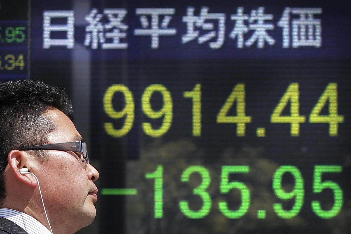 A man walks in front of the electronic stock board of a securities firm showing Japan's Nikkei 225 index fallen 135.95 points to 9914.44 in Tokyo Wednesday, April 4, 2012. Asian stock markets on Wednesday followed Wall Street into negative territory after