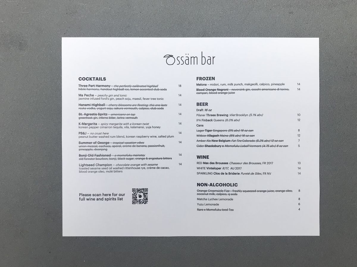 A white piece of paper with black lettering displaying the restaurant's drinks menu set on a gray table