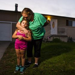 Kristen Morales, kissing her daughter, Sophia, 6, gets emotional as she describes her relationship with one of the victims of a triple homicide, Heike Poike, at 639 N. Sir Philip Drive in Salt Lake City on Saturday, Sept. 19, 2015.