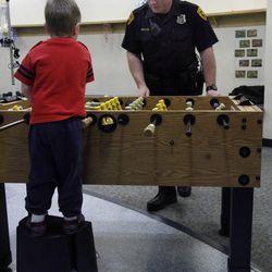 Salt Lake police officer Josh Ashdown plays foosball with a child at Primary Children's Medical Center in Salt Lake City on Thursday, Jan. 19, 2012.