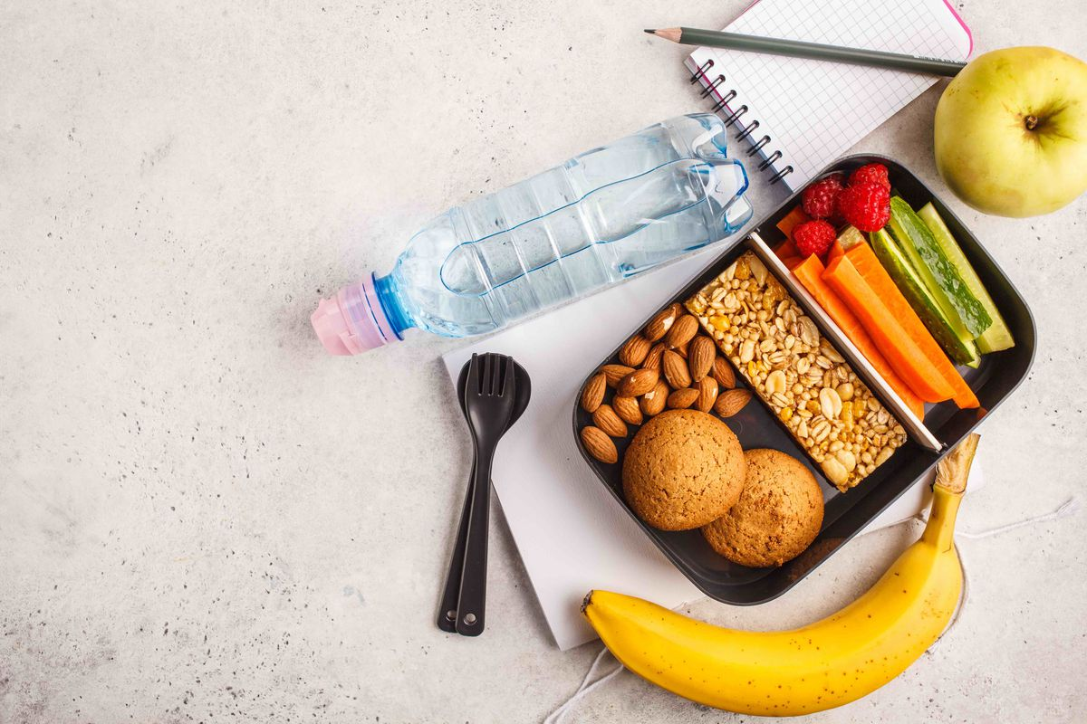 container with dividers for food next to a spoon, banana, apple, bottle of water, and notebook