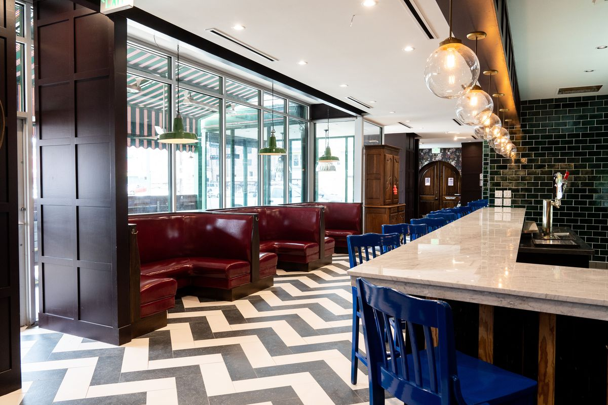 the interior of a bar with marble bar top, black and white zigzag tile on the floor, and dark red leather booths agains a wall of windows