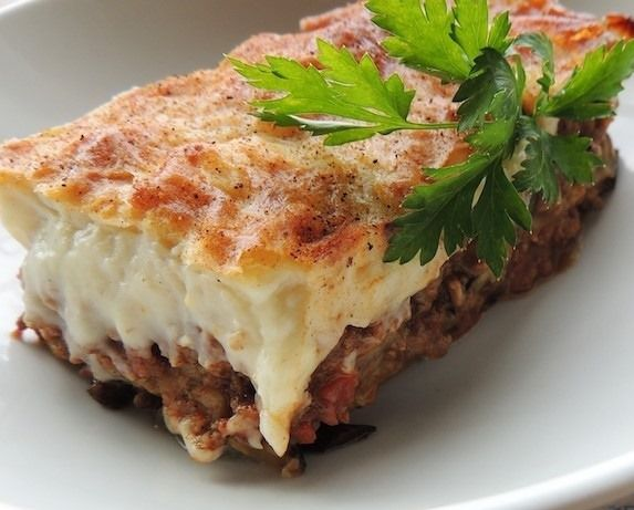 A slab of mousakka with a bottom layer of eggplant topped by a thick oozy layer of creamy sauce and pasta with a golden crust on top