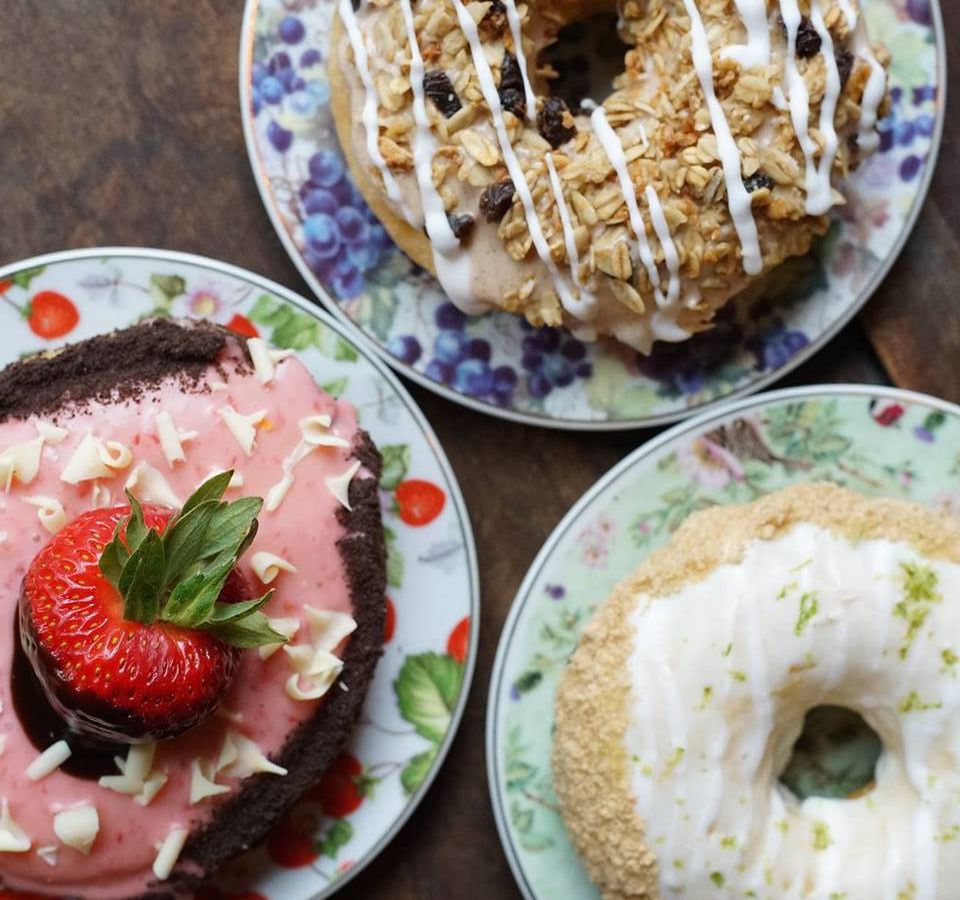 Three doughnuts, one with strawberry topping, one with white glaze and another with fruit and drizzle
