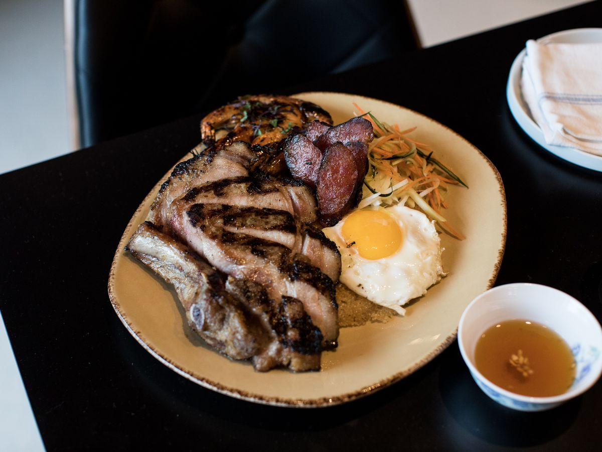 A plate of sliced pork chops with broken rice.