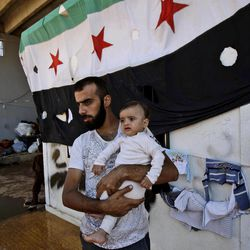 In this Wednesday, Sept. 12, 2012, photo, a Syrian man, who fled his home due to government shelling, holds his son as they take refuge at Bab Al-Salameh crossing border, hoping to cross to one of the refugee camps in Turkey, near the Syrian town of Azaz. The days are still hot across the fertile plains of northern Syria, but at night there is a hint of a chill an ominous harbinger of winter's approach and the deepening of the humanitarian crisis gripping a country wracked by civil war.