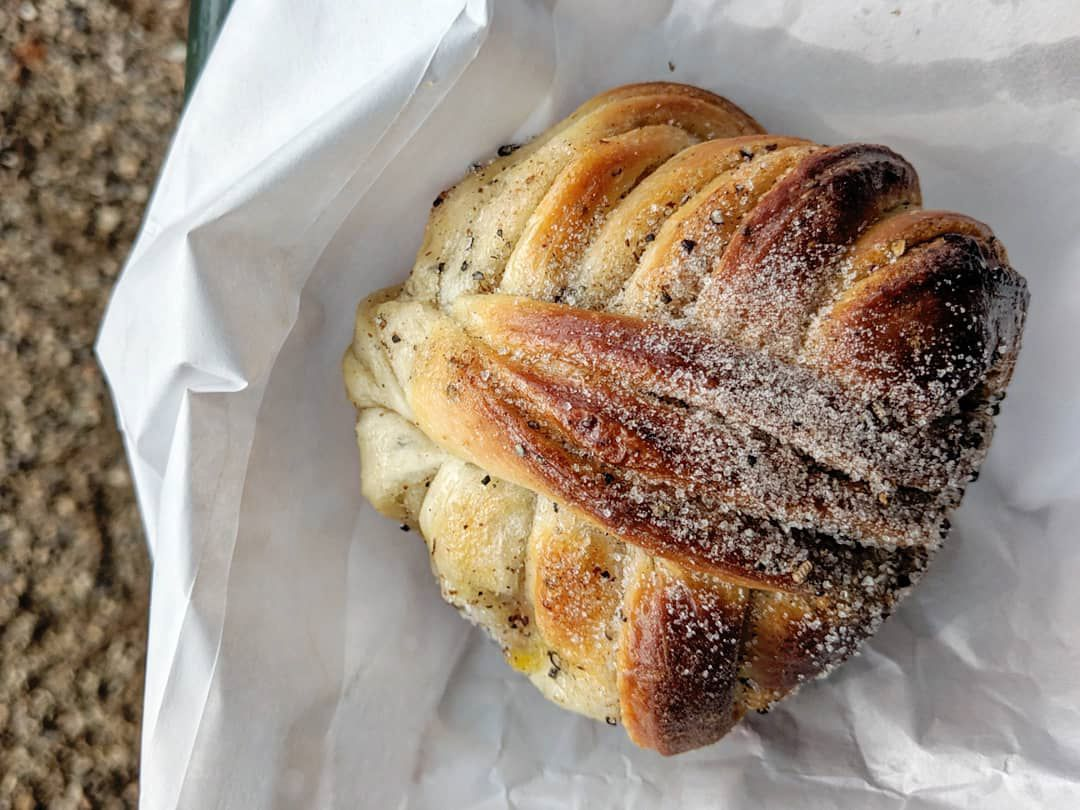 A close-up on a sugar-dusted, knotty cardamom bun resting on a paper bag