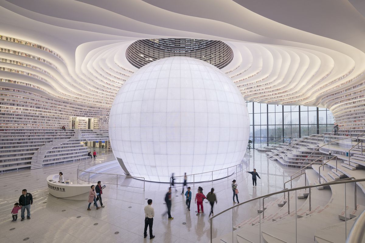 A glowing orb sits at the center of the main floor of a massive space, with curving bookshelves running up the walls and extending to the ceiling on either side.