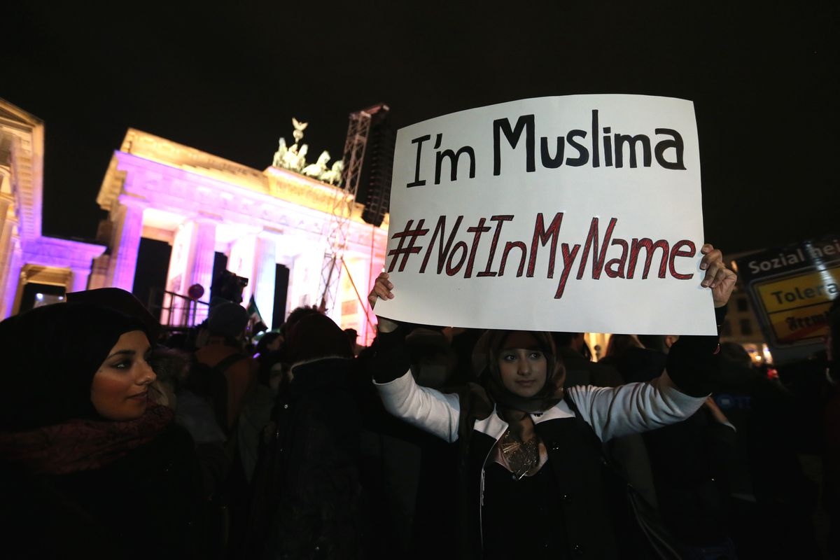 A woman shows a banner reading during a Muslim community tolerance rally on January 13, 2015 in front of Brandenburg Gate in Berlin.