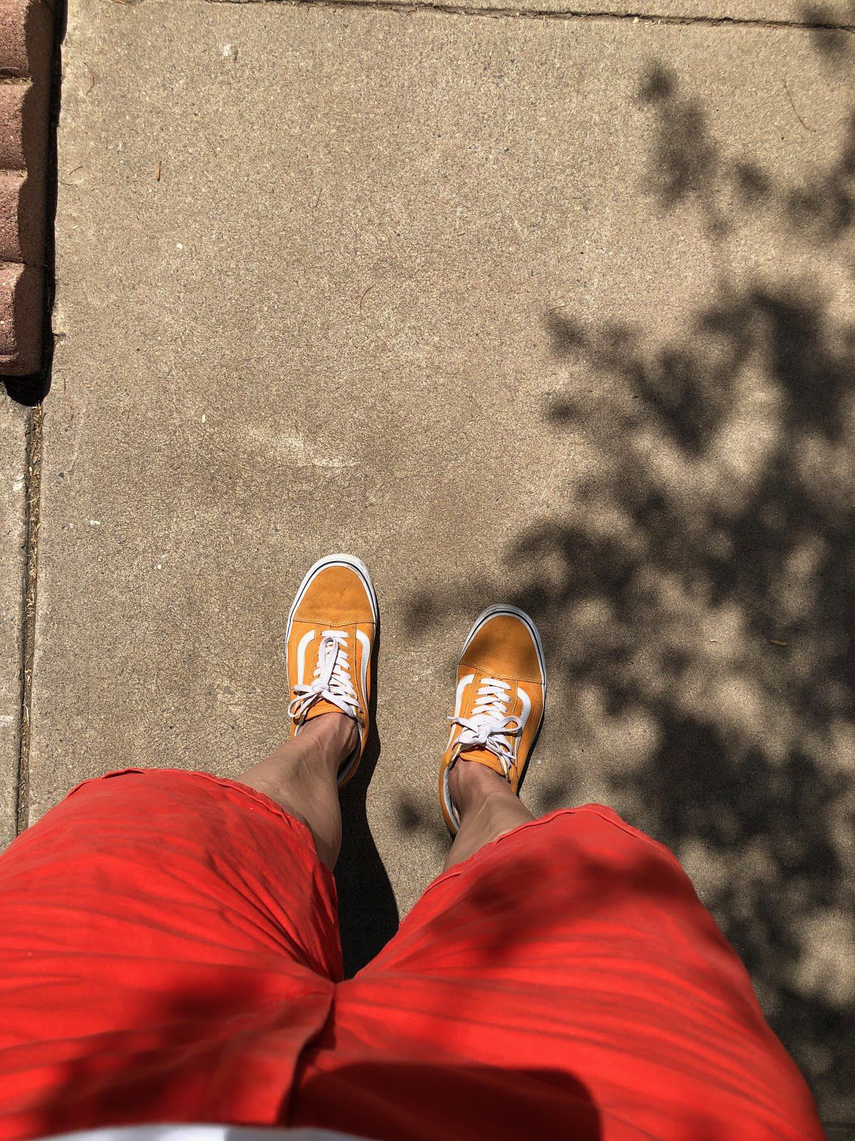 A photo taken from the perspective of the person wearing them shows a pair of bright orange shoes on the sidewalk.