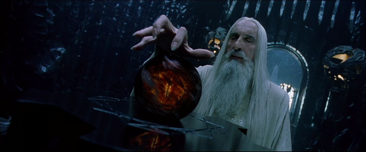 Saruman gestures with his hand claw-like over the Palantir — which shows the eye of Sauron wreathed in dark smoke — in The Lord of the Rings: The Fellowship of the Ring.