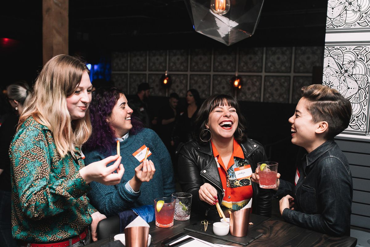 Four queer people hold drinks and laugh around a bar table.