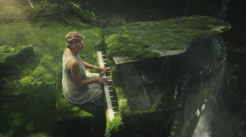 """Taylor Swift sits at her piano in a forest in the music video for """"Cardigan."""""""